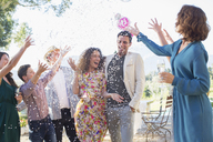 Family throwing confetti on newlywed couple - CAIF17266