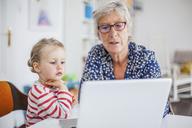 Grandmother and granddaughter using laptop - KVF00096