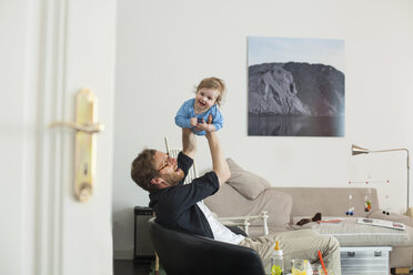 Father lifting up his daugther in living room - KVF00099