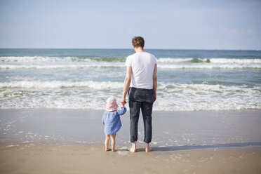 Netherlands, Renesse, father and daughter standing at beach - KVF00108