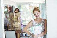 Businesswoman carrying binders in office - CAIF17308