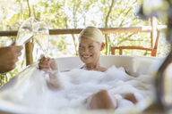 Couple toasting each other in bubble baths - CAIF17374