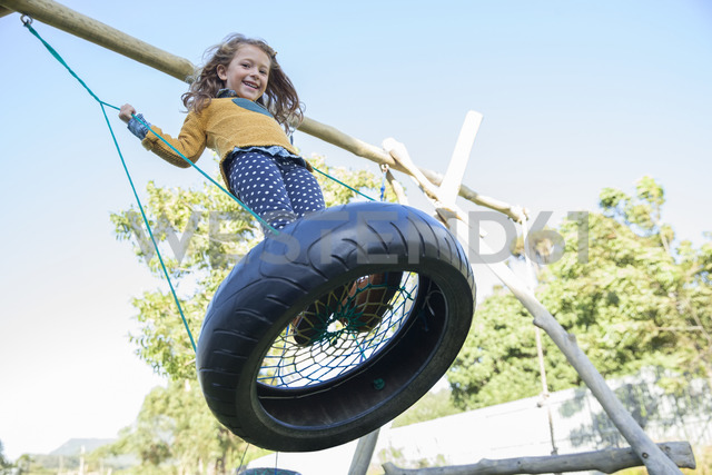 Girl playing on tire swing - CAIF17469