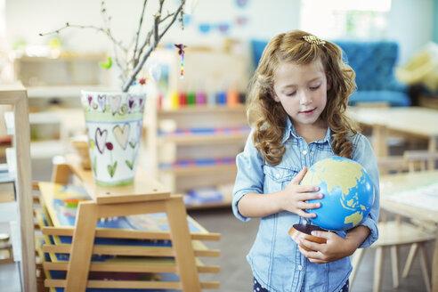 Student examining globe in classroom - CAIF17481