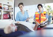 Paramedic and nurse examining patient in ambulance - CAIF17511