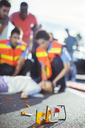Paramedics examining injured girl on street - CAIF17523