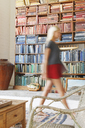 Blurred view of woman walking by bookcase - CAIF17550
