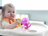 Baby girl playing with sippy cup in high chair - CAIF17556