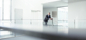Businessman standing at railing in office - CAIF17607