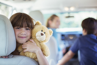 Portrait of happy girl with teddy bear in back seat of car - CAIF17679