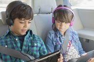 Brother and sister with headphones using digital tablets in back seat of car - CAIF17688