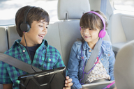 Happy brother and sister with headphones using digital tablets in back seat of car - CAIF17691