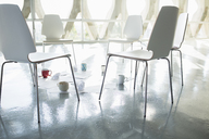 Coffee cups and paperwork at circle of chairs - CAIF17733