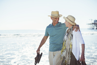 Senior couple walking on beach - CAIF17739