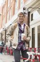 Man drinking coffee on city street - CAIF17757