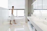 Man in towel walking in bathroom - CAIF17883