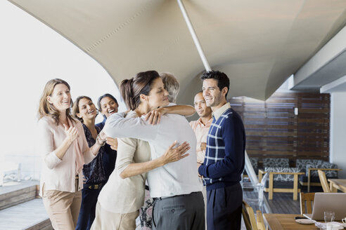 Business people hugging in office - CAIF17913