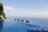 Lounge chairs in infinity pool overlooking ocean - CAIF17931