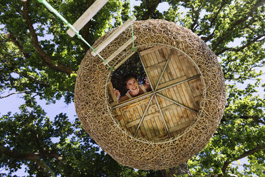 Woman smiling in modern treehouse - CAIF17949