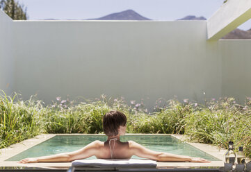 Woman relaxing in luxury lap pool - CAIF17964