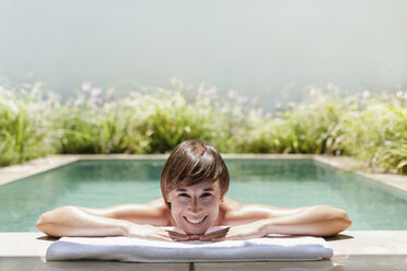 Woman relaxing in luxury lap pool - CAIF17967