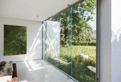 Modern house with glass walls overlooking grass - CAIF17970