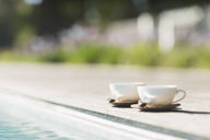 Cappuccino cups at poolside - CAIF17985