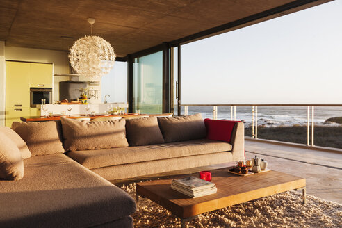 Sofa and coffee table in modern living room overlooking ocean - CAIF17988