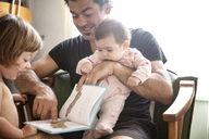 Father reading book to daughters while sitting on chair at home - CAVF09158