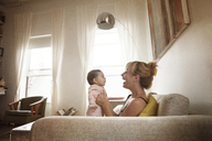 Side view of mother playing with daughter while sitting on sofa at home - CAVF09170