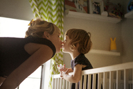 Girl kissing mother while standing in crib at home - CAVF09197