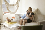 Happy family sitting on sofa at home - CAVF09200