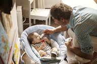 Father feeding popsicle to baby girl at home - CAVF09206