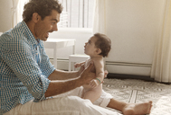 Father playing with baby girl at home - CAVF09209