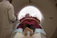 Patient undergoing CAT scan while looking at doctor in hospital - CAVF09278