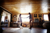 Side view of couple holding hands while standing at home - CAVF09317