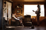 Man playing guitar while woman relaxing on chair at home - CAVF09320