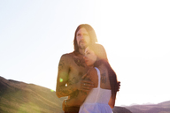 Couple looking away while embracing against clear sky - CAVF09326