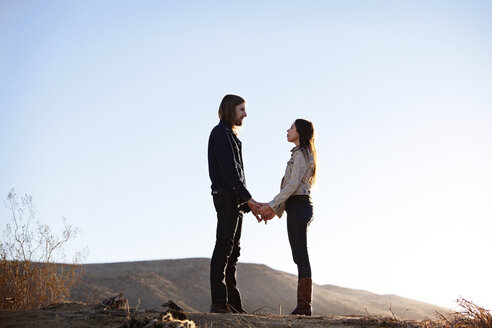 Couple holding hands while standing face to face on field against clear sky - CAVF09332