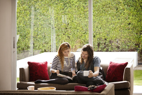 Couple reading magazine while sitting on sofa at home - CAVF09368
