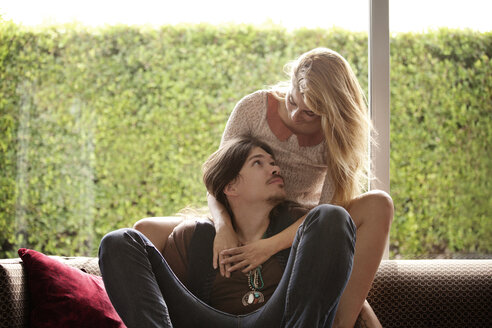Couple sitting on sofa against window at home - CAVF09371