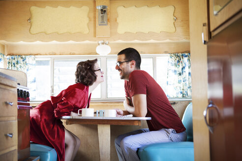 Side view cheerful couple sitting by table in camper van - CAVF09395
