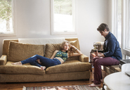 Man playing guitar while woman lying on sofa at home - CAVF09497