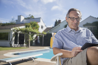 Man using digital tablet at poolside - CAIF18000