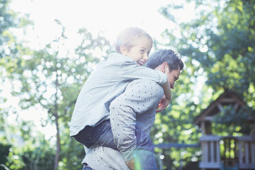 Father carrying son piggyback outdoors - CAIF18009