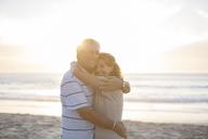 Senior couple hugging on beach - CAIF18054