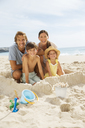 Family sitting in sandcastle on beach - CAIF18066
