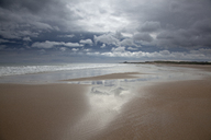 Clouds reflected in water on beach - CAIF18075