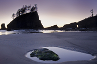 Silhouette of cliffs on beach at low tide - CAIF18093