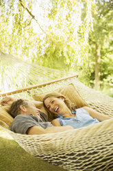 Couple relaxing in hammock outdoors - CAIF18102